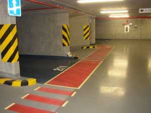 Malované dopravní značení na podlaze podzemních garáží, červený pruh pro chodce, žluto černé šrafování na betonových sloupech