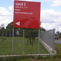 Čtvercová červená cedule s bílým informačním značením, připevněná na sloupech plotu kolem stromů a trávníku, v pozadí odjíždějící automobil, obloha s mraky