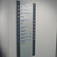 Modulový orientační panel, bílý střed s lepenými nápisy, šedé okraje s šipkami a značeními, přimontováno na bílé zdi zdravotnického zařízení