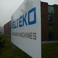 Pohled zprava na bílou dibond desku potištěnou logem VELTEKO a nápisem PACKAGING MACHINES, instalovaná na dvou kovových sloupech, v pozadí hnědá moderní budova s okny, bílé nebe