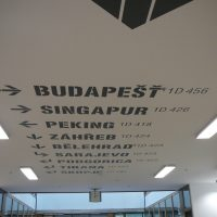 Názvy světových měst s orientačním značením na bílém stropě, malovaná grafika