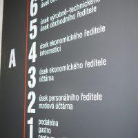 Černá informační deska budovy A, bílé značení pater 1–6 s popisem úseků