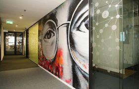 Fototapeta na kancelářské příčce s detailem očí Johna Lennona, po stranách skleněné příčky s polepem z plotrované pískované folie s motivem souhvězdí