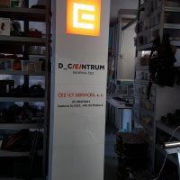 Hliníkový LED panel stojící na zemi v interiéru, svítící logo ČEZ, označení firem