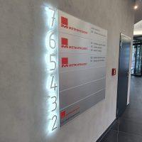 Boční pohled na hliníkový panel se značením budovy na zdi, 3D svítící číslice jako označení pater