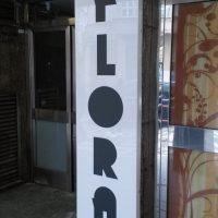 Bílý světelný plexi panel umístěný na sloupu, na přední straně černé logo REZIDENCE FLORA