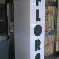 Bílý světelný plexi panel dvojstranný, umístěný kolem sloupu, na přední straně černé logo REZIDENCE FLORA