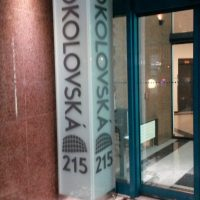 Kvádrový svítící LED box z mléčného skla, horizontální nápis SOKOLOVSKÁ 215, umístěn v rohu před skleněnými dveřmi