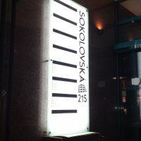 Skleněný bílý svítící LED panel, černý horizontální nápis SOKOLOVSKÁ 215, černé přímky, přišroubováno na zdi