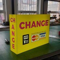 Box tvaru kvádru žluté barvy v horní části a na levém boku s červeným nápisem change, níže s logy firem Mastercard a Visa a piktogramem bankomatu, stojící na stole ve výrobně