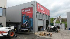 Dva bannery v rámu na šedé budově garáží, reklama s logem firmy Bobcat, nápisem One Tough Animal a ilustrací strojů na stavbě