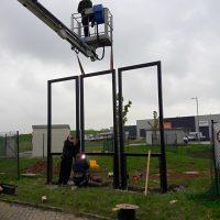 Technici provádí betonáž černých kovových rámů na trávník pomocí vysokozdvižné plošiny