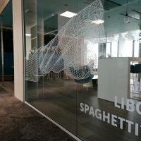 Bílé geometrické tvary a nápis JE LIBO SPAGHETTI?, inkoustová grafika nalepená na skleněné stěně moderního restauračního zařízení