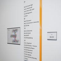 Bílá informační tabule z plexiskla s oranžovým pruhem na pravé straně, s černým informačním textem, nalepená na bílé zdi, vedle tabulka s orientačním plánem budovy a tabulka s číselným označením