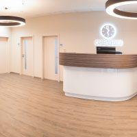 Prostředí moderní čekárny ordinace, uprostřed recepční pult nahoře dřevěný a dole bílý, vlevo červená křesla a bílé stolky, na zadní stěně bílé dveře do jednotlivých místností, nahoře kruhová obrysová světla, na zadní stěně nad recepcí podsvícené logo a nápis CARE MEDICO