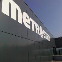 Bílé logo firmy Metrostav z hliníkového dibondu připevněné na vnější černé plastové fasádě nové budovy.