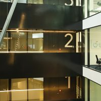Označení pater 1–3 v oknech budovy, bílé číslovky na černém podkladě, prosklené stěny budovy, černé balkony
