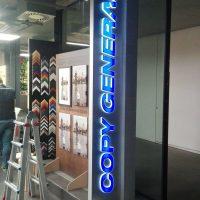 Vertikálně postavený bílý box s modrým LED podsvíceným nápisem COPY GENERAL, umístěno v rohu prodejny za prosklenou stěnou