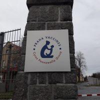 Stříbrná čtvercová cedule s gravírovaným logem PRAHA VACCINES, modrá silueta ženy a dítěte, kamenný sloup, kovová mříž plotu
