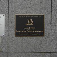 Bronzová pamětní deska na mramorovém obkladu budovy, nápis Award 2002 for Outstanding Concrete Structures, zlaté písmo a rám