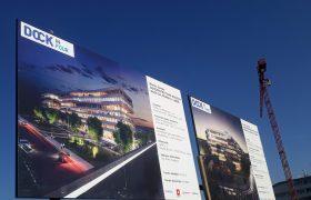 Dvě velkoplošné cedule na staveništi s vizualizací budoucích staveb administračních budov DOCK, v pozadí modré nebe a jeřáb