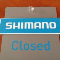Šedá cedulka na dveře s bílo-modrým nápisem SHIMANO a nápisem closed, pro označení otevřeno/zavřeno, s přísavným terčíkem nahoře, na hnědém pozadí
