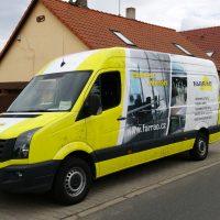 Z pravého předního rohu vyfocená žlutě polepená dodávka, na boku bílo-šedá reklamní plocha firmy farrao.cz, v exteriéru před domem