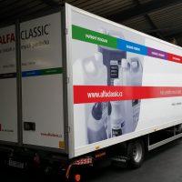 Ze zadního pravého rohu vyfocené nákladní vozidlo, na nákladní skříni zezadu tmavý nápis ALFACLASSIC a další menší tmavé nápisy, v prostředku barevný pruh, dole loga a web, na boku v levé části černobílá fotka kanystrů a jiných nádob, přes celou skříň v dolní části červený pruh s bílými nápisy, v horní části zeleno-modro-fialovo-červený pruh s bílými nápisy, v prostředí haly