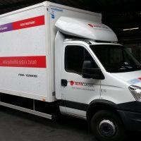 Zboku vyfocené bílé nákladní vozidlo, na předních dveřích i kapotě červeno-černé logo ALFACLASSIC, na nákladní skříni v levé části černobílá fotka kanystrů a jiných nádob, přes celou skříň v dolní části červený pruh s bílými nápisy, v horní části zeleno-modro-fialovo-červený pruh s bílými nápisy, v prostředí haly