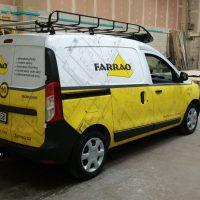 Ze zadního pravého boku vyfocené menší auto dodávkového typu, celopolepené žluto-bílé, v prostoru dílny