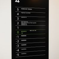 Černá tabule s bílým a zeleným orientačním značneím pater budovy, připevněno na bílé zdi
