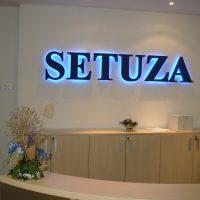 Černý 3D nápis SETUZA modře podsvícený, umístěný na bílou stěnu v interiéru, pod logem tři světle dřevěné skříňky, v popředí recepční pult, v pozadí napravo i nalevo dvoje dveře otevřené