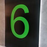 Černý panel zezadu podsvícený LED světlem, na panel velká zelená číslovka 6, na šedé stěně