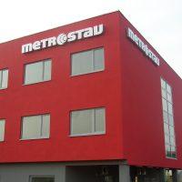 Červená budova tvaru kvádru s velkými prosklenými okny a šedým suterénem, napravo podepřena sloupy, nahoře zpředu i zprava velké bílé logo firmy metrostav