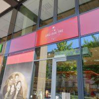 Skleněná stěna, uprostřed 3 červené obdélníky, na prostředním bílý nápis UNO DUE TRE, vlevo další reklamní plochy