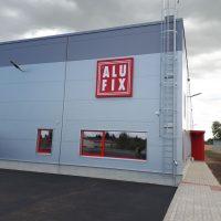 Čtvercový červený panel s nápisem ALU FIX, přichycený na stěnu šedé kvádrové budovy