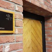 Černý dibondový štítek v dřevěném rámečku, nápis Šatna a logo Czech Equestrian Team, přilepeno na cihlové zdi budovy vedle dřevěných dveří s černým rámem