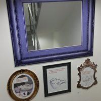 Čtvercové zrcadlo s mohutným modrým historickým rámem, pod ním vlevo šedobílý obraz ve zlatém kulatém rámu, vprostřed šedobílý obraz v černém obdélníkovém rámu a vpravo šedobílý obraz v rámu tvaru erbu, vše na bílém podkladu, v mezipatře u schodiště, které se odráží v zrcadle, nahoře zářivka