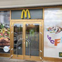 Reklamní označení vstupu do MC Donald's, 3D žluté logo nad skleněnými dveřmi, polep výlohy barevnou samolepicí okenní folií