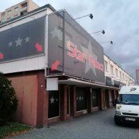 Roh budovy, vpravo i vlevo černý banner s šedými hvězdami a červenými šipkami, oba bannery doplněny osvětlením, dolní část budovy se zakrytými okny, vpravo bílá dodávka, v pozadí panelové domy, vlevo keř a poštovní schránka