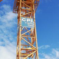 Detail oranžového jeřábu, mezi jednotlivými částmi konstrukce natažený banner, modrý s bílým nápisem CPI, v pozadí modrá obloha s mraky
