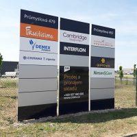 Tři deskové informační stojany s prezentací firem v areálu Průmyslová 479, loga, názvy, reklamní nabídky, zelený drátěný plot