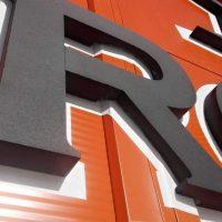 Detail písmene R z 3D černého loga s bílými obrysy, zhotoveného z extrudovaného polystyrenu, přilepeného na vnější fasádu oranžové barvy.