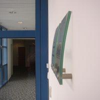 Detailní pohled zprava na navigační štítky z ohýbaného skla, přišroubované ve spodní části distančními šrouby na stěnu chodby, vzadu skleněné dveře s modrými rámy