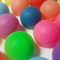 Detailně zachycené barevné pingpongové míčky s vytečkovaným obvodem čísla dvě