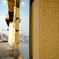Detailní pohled zboku na informační panel z bezpečnostního skla Connex, připevněno nerezovými distančními šrouby na zdi budovy ordinace