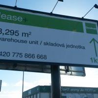 Pohled zespodu na dvojitý reklamní billboard, dibond deska s potištěnou folií, černý rám a sloup, tři světla instalovaná na vrchu. V pozadí část budovy HOPI a reklamní cedule SCANIA, obloha