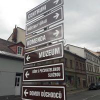 Šest hnědých směrových tabulek na sloupu dopravního značení, navigace k hlavním městským institucím, řada špinavých starých domů