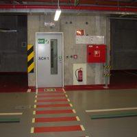 Dopravní značení uvnitř garáže, informační nápis SCH1 a tabulka EXIT na dveřích, dopravní značení a číslování parkovacích míst na podlaze, tabulky s fotoluminiscencí na zdi