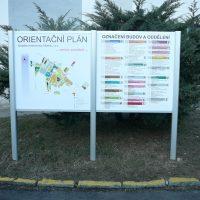 Dvoudílný hliníkový stojan, orientační systém, plán budov a seznam oddělení nemocnice, žluté dopravní značení, okrasné keře